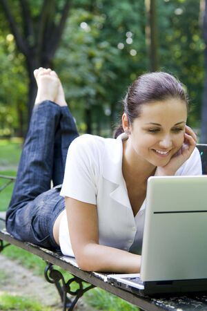 Woman using laptop on bench outdoors photo
