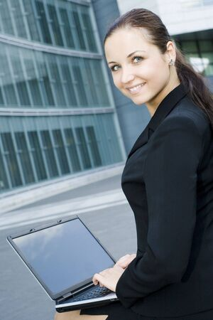Businesswoman using laptop outside office photo