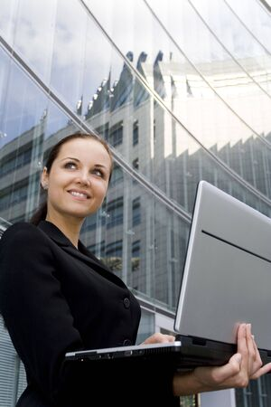 Businesswoman using laptop outside office Stock Photo - 3463583