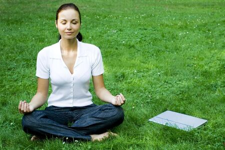 Meditating woman with laptop photo