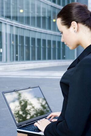 Businesswoman using laptop outside office Stock Photo - 3498829