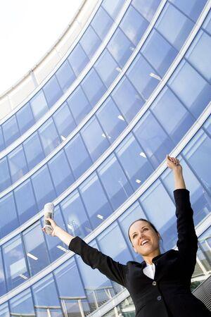 Businesswoman Raising Arms at Skyscraper photo
