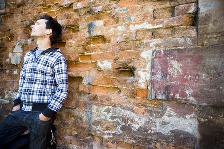 Man leaning against brick wall
