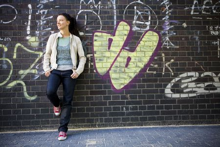 freetime: Woman leaning against brick wall with graffiti