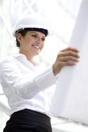 Woman wearing a hardhat holding plans Stock Photo - 3520561