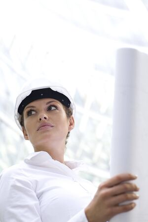 Woman wearing a hardhat holding plans photo