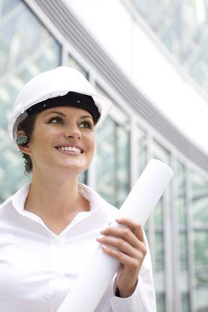 Female architect holding blueprints photo