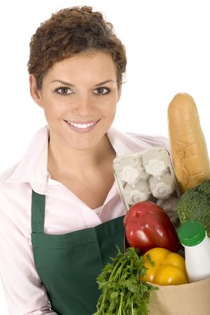 Woman in apron holding grocery bag Stock Photo