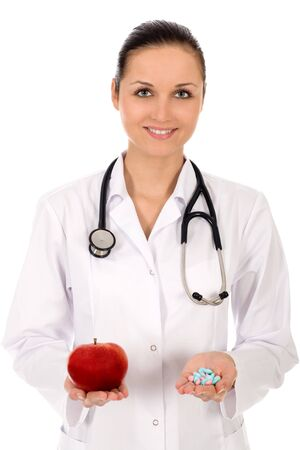 Doctor holding apple and pills photo