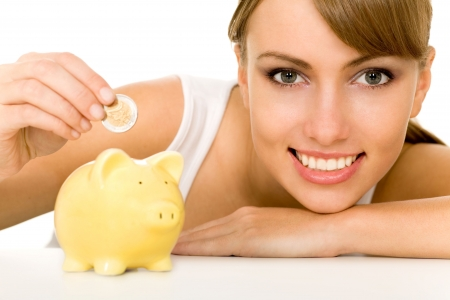 Woman putting coin in piggy bank Stock Photo - 3904234