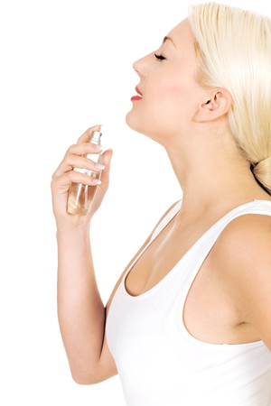 Woman spraying perfume on neck photo