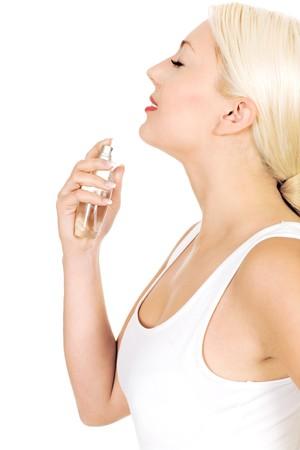 Woman spraying perfume on neck photo