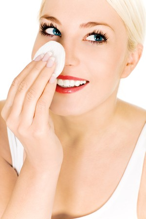 Woman using cotton pad on face photo