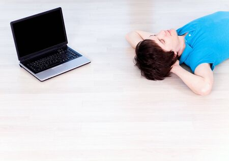 Man lying on floor with laptop photo