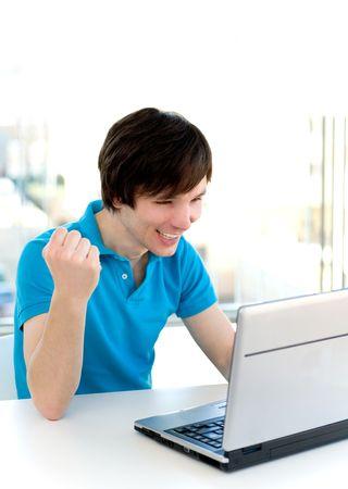 clenching: Man using laptop, clenching fist Stock Photo