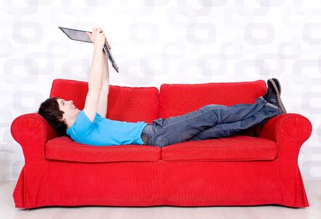 Young man lying on couch with laptop