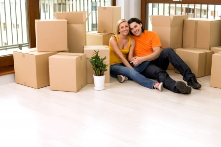 family moving house: Couple sitting in new home