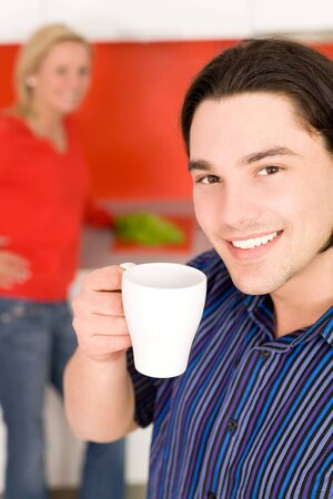 Couple in kitchen, man holding coffee cup photo