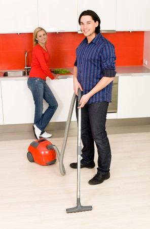 Man vacuuming, woman in background photo