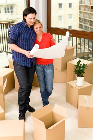 Couple looking at blueprints in new house photo