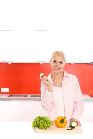 Smiling woman with vegetables in a kitchen photo