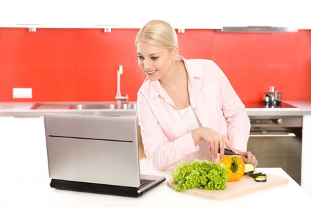 Woman with laptop preparing food Stock Photo - 4610864