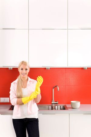 dish washing gloves: Woman wearing rubber gloves standing in kitchen