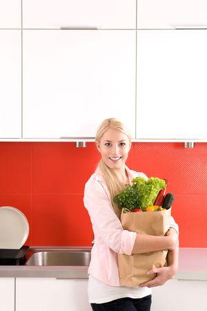 bolsa supermercado: Mujer llevando la bolsa de comestibles en la cocina Foto de archivo