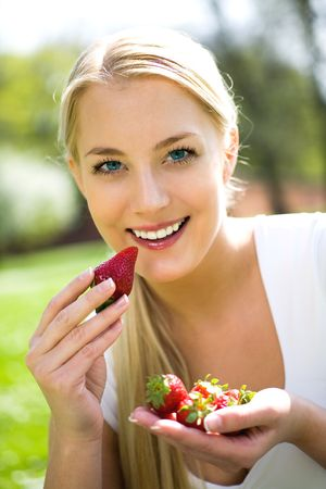 outdoor eating: Woman eating strawberries