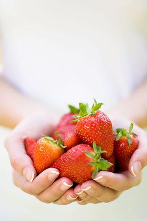 strawberries: Hands holding strawberries