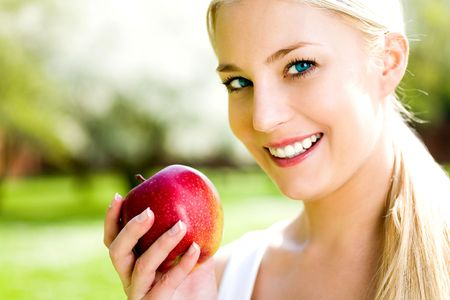 woman eat: Young woman holding red apple