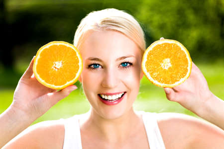 Woman holding two halves of orange  photo