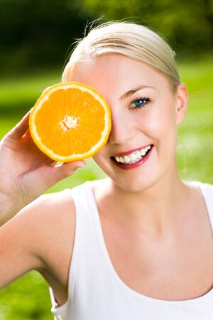 Woman holding orange over eye photo