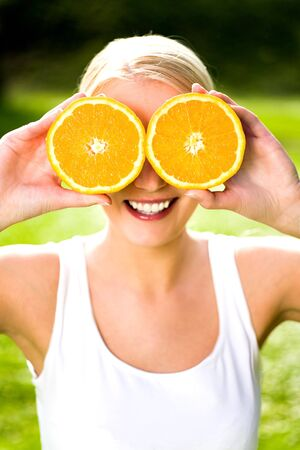 Woman holding orange over eyes photo