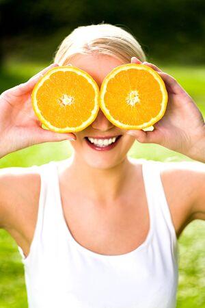 Woman holding orange over eyes Stock Photo