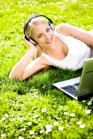Woman with headphones and laptop outdoors photo