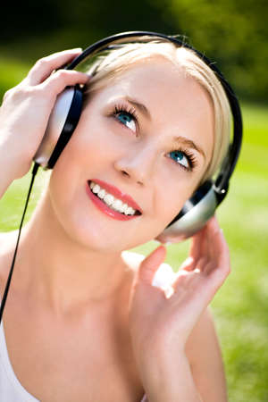 Woman listening to headphones outdoors photo