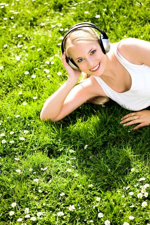 Woman lying on grass with headphones Stock Photo - 4814555