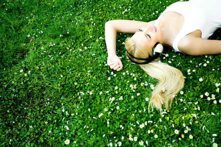 Woman lying on grass with headphones photo