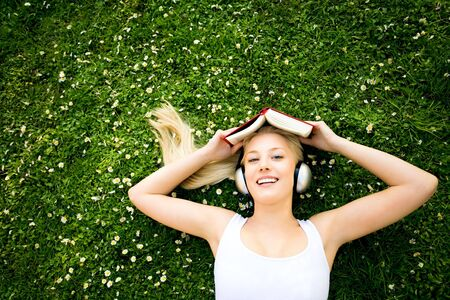 Woman lying on grass with book and headphones photo