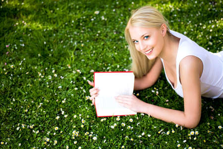 Woman lying on grass with book photo