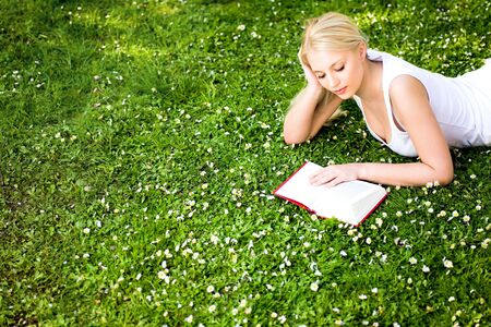 Woman lying on grass, reading book