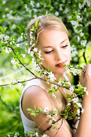 Woman by flowers on tree photo