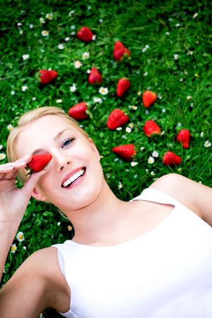 Young woman lying on grass with strawberries photo