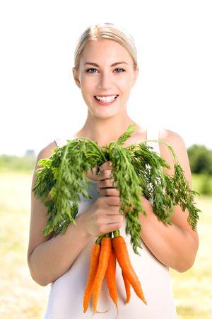 zanahoria: Mujer con manojo de zanahorias Foto de archivo