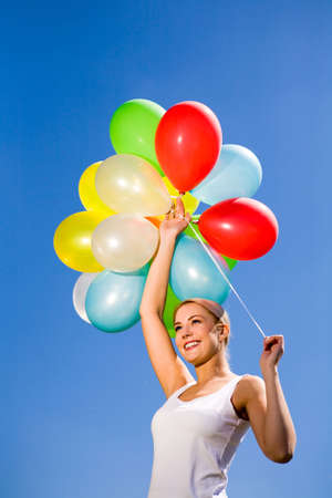 Woman holding balloons against blue sky Stock Photo - 4969558