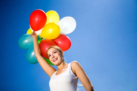Woman holding balloons against blue sky photo