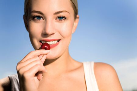 Young woman eating cherry