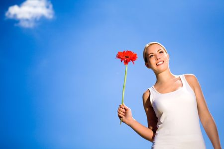 Woman holding flower against blue sky photo