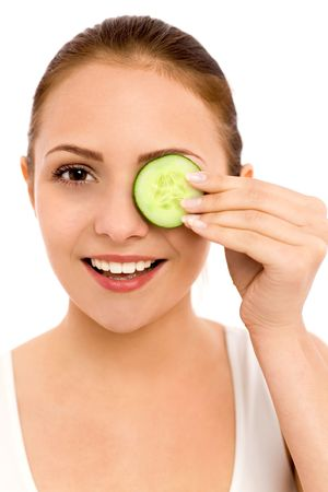 Woman holding slice of cucumber over eye